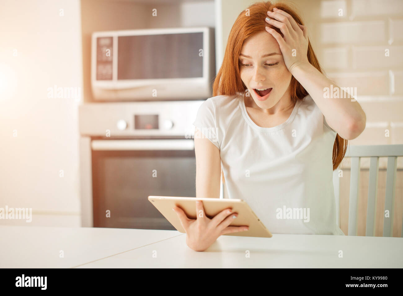 redhair girl happy smiling on digital table with wining something Stock Photo