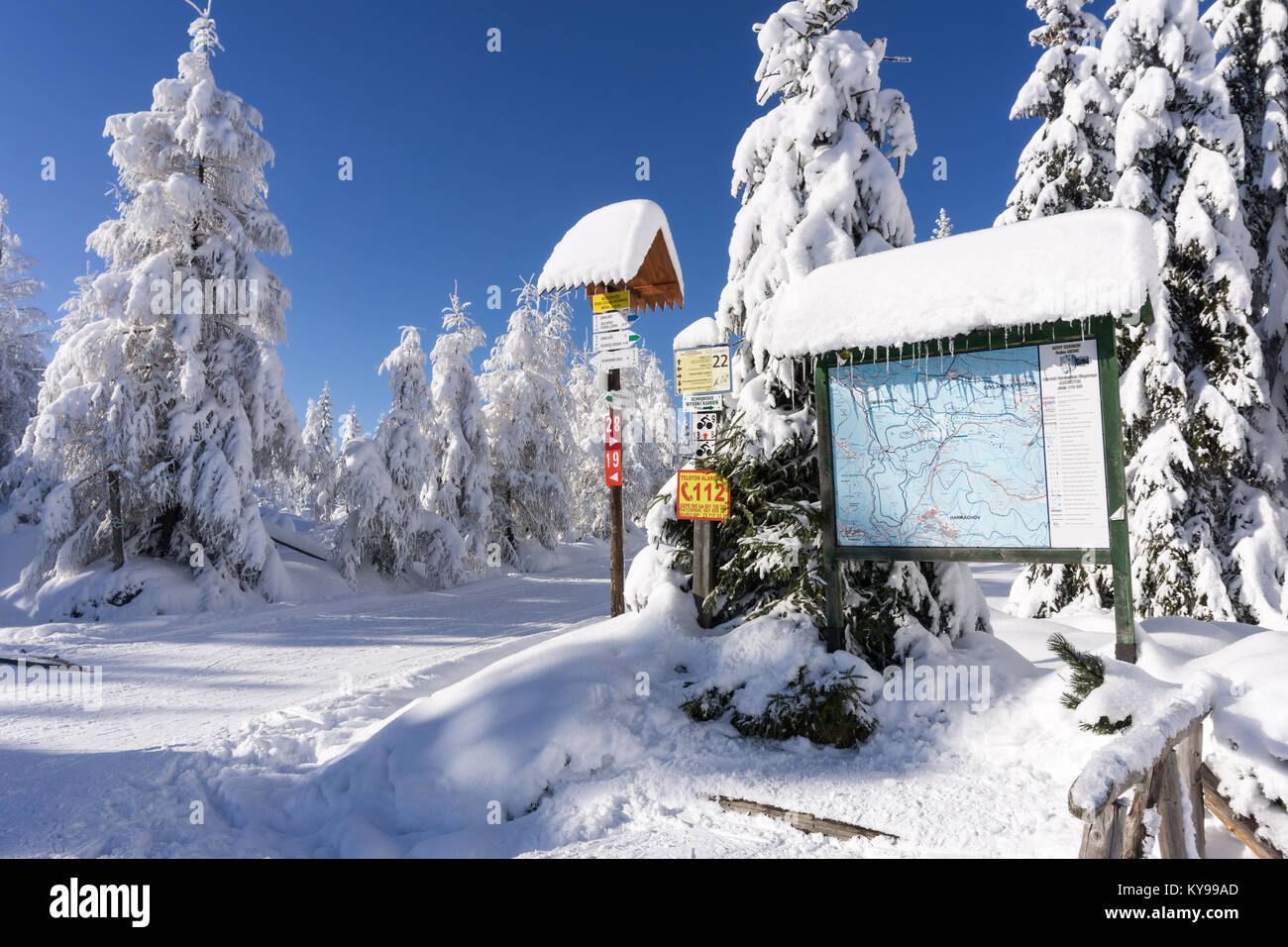 Mountain trail sign with directions and hiking or skiing time in Jakuszyce, Karkonosze (Giant Mountains), Poland. - Stock Image