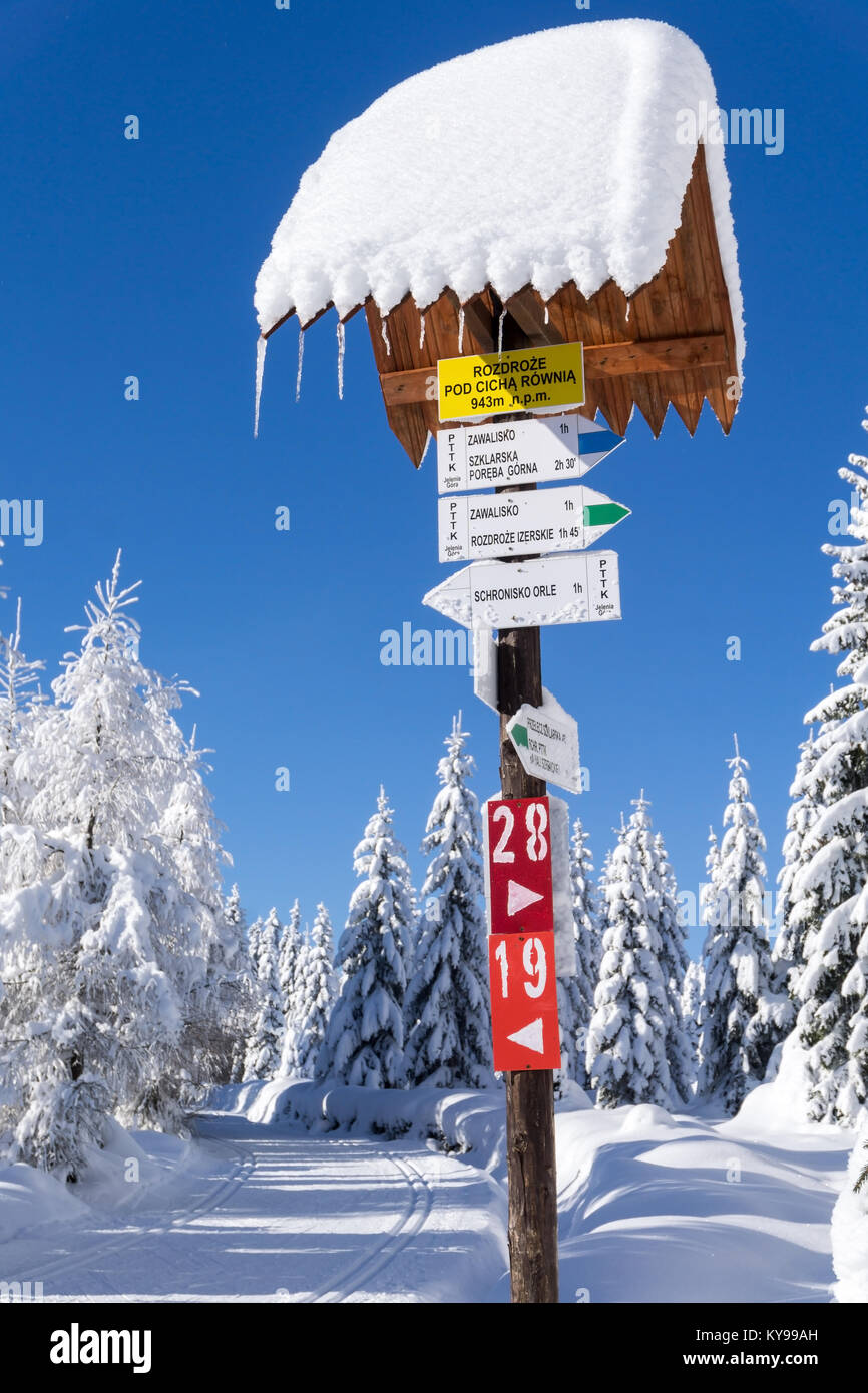 Mountain trail sign with directions and hiking or skiing time in Jakuszyce, south Poland. Winter mountain road with - Stock Image