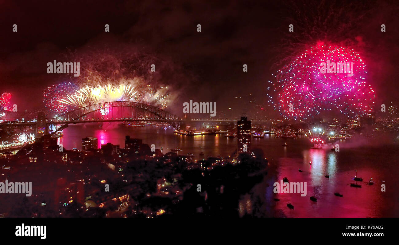 Bright light balls and fire shapes during Sydney New year fireworks over city CBD landmarks on shores of Sydney - Stock Image