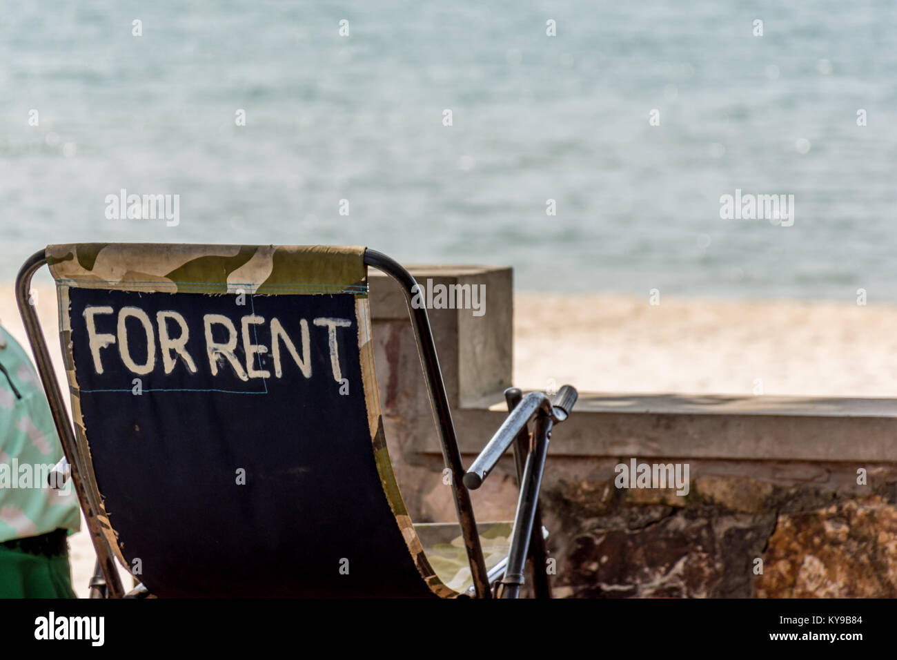 Beach side deck chair labeled For Rent facing out on to the beach. - Stock Image
