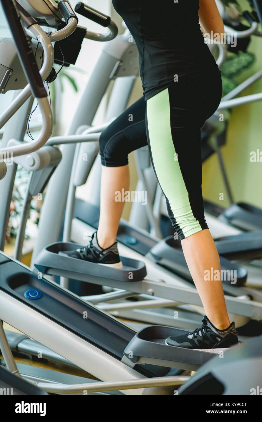 Legs on elliptical trainer - Stock Image