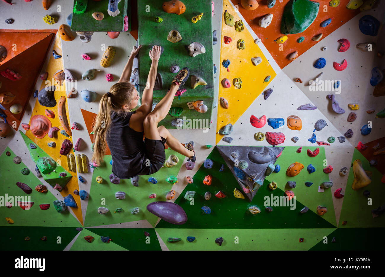 Young woman bouldering on overhanging wall in indoor climbing gym - Stock Image