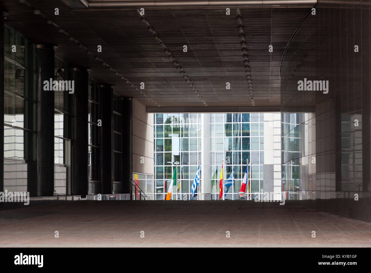 The European Parliament buildings in Brussels, Belgium with lots of European flags seen through a tunnel under the - Stock Image