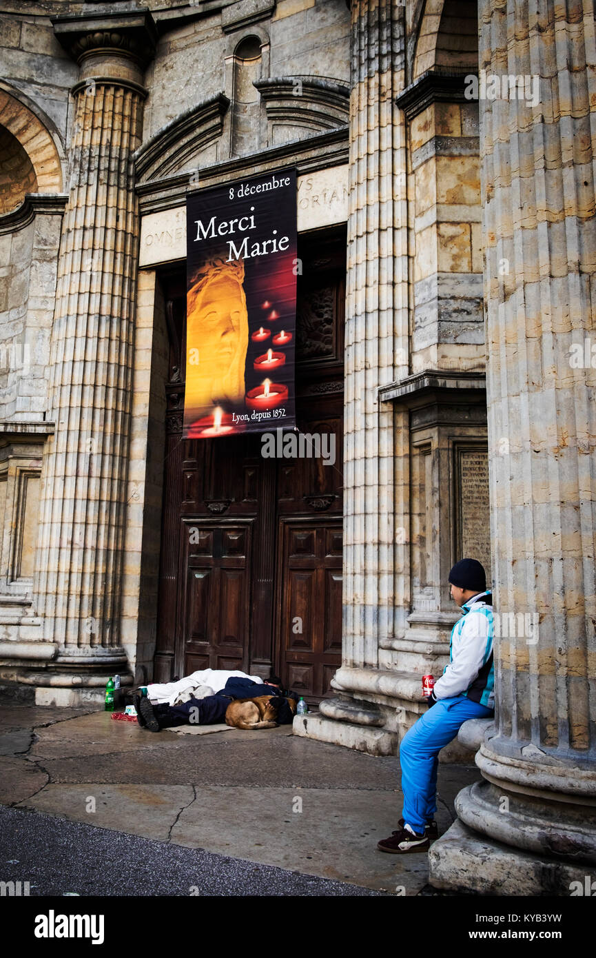 Two homeless men sleep with their dogs outside a church in the centre of Lyon, France. The banner above says 'thank - Stock Image