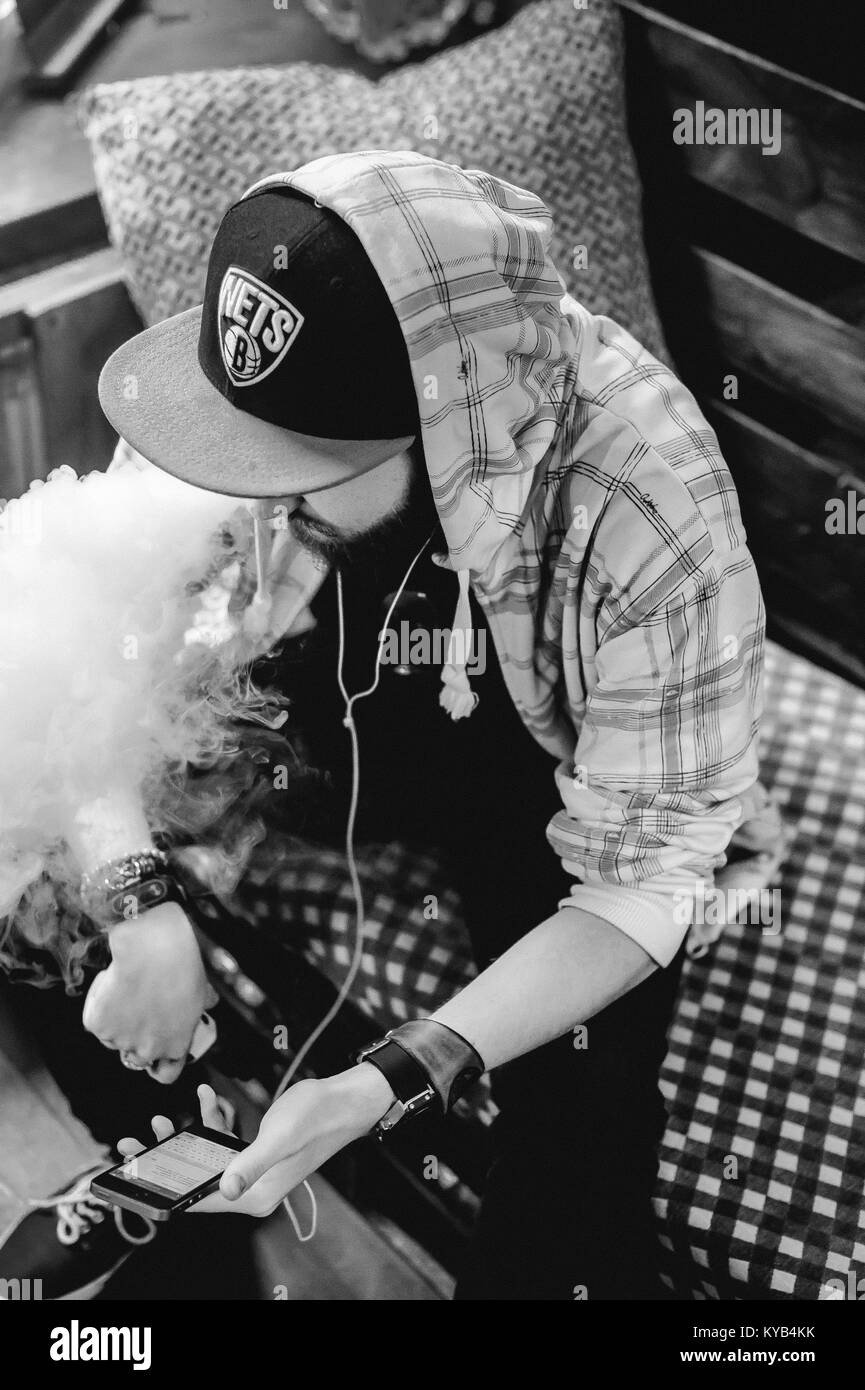 young man with beard in light checkered jacket with hood in a cap smokes an electronic cigarette and listens to - Stock Image
