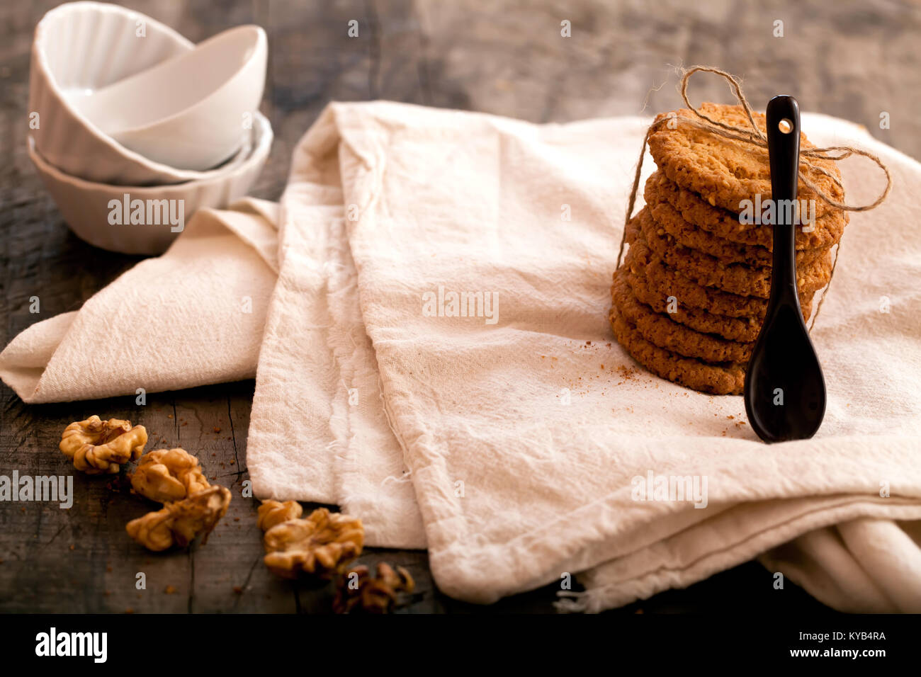 Home walnuts biscuits on a wooden background. Sugary baked biscuits with walnuts. Closeup - Stock Image