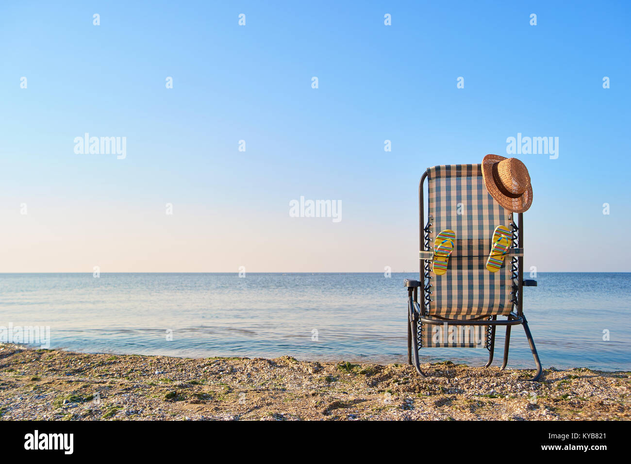 Back view woman's hat on deck chair and attached flip flops. - Stock Image