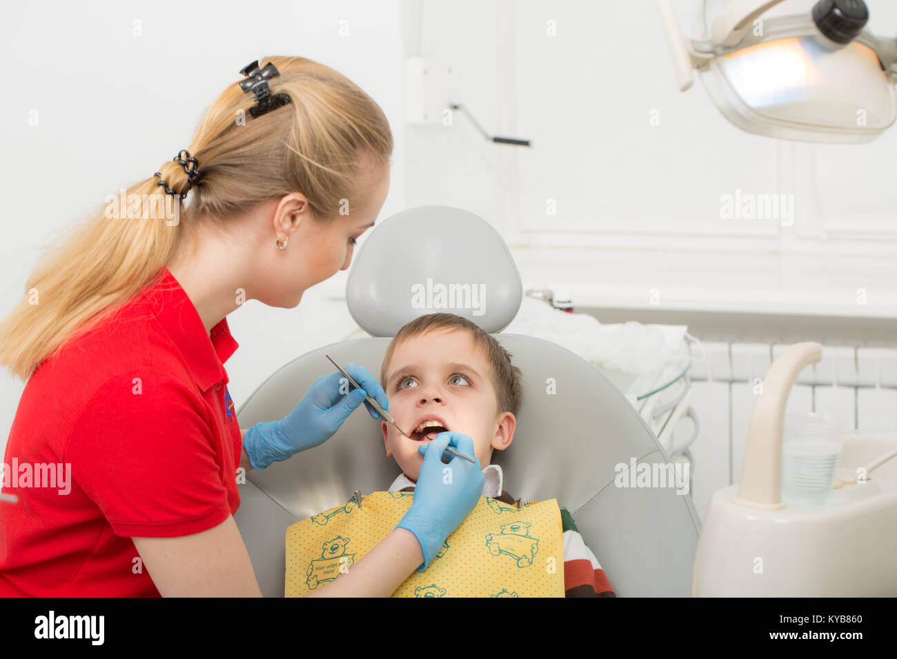 Female dentist examines the teeth of the patient child. Child mouth wide open in the dentist's chair. Close-up. Stock Photo