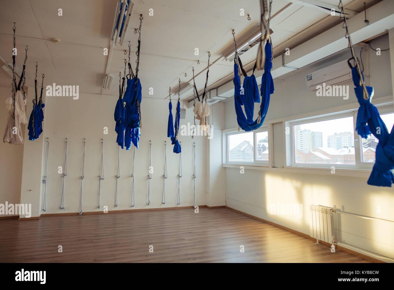 Hanging hammocks in gym for aerial anti-gravity yoga - Stock Image
