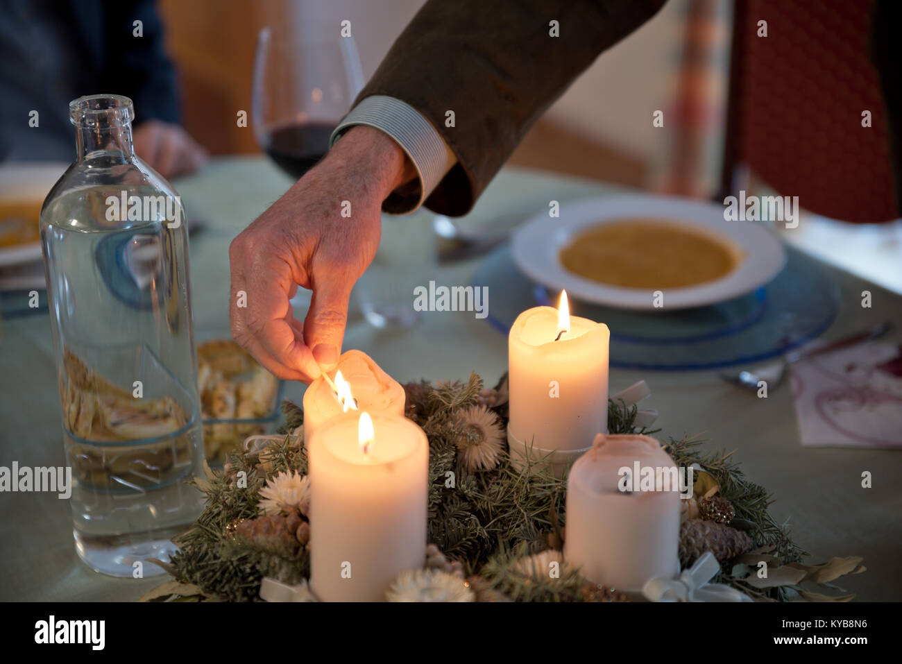 Person lighting the candles on a richly decorated Advent wreath with a match on a solemnly laid table, ready for - Stock Image