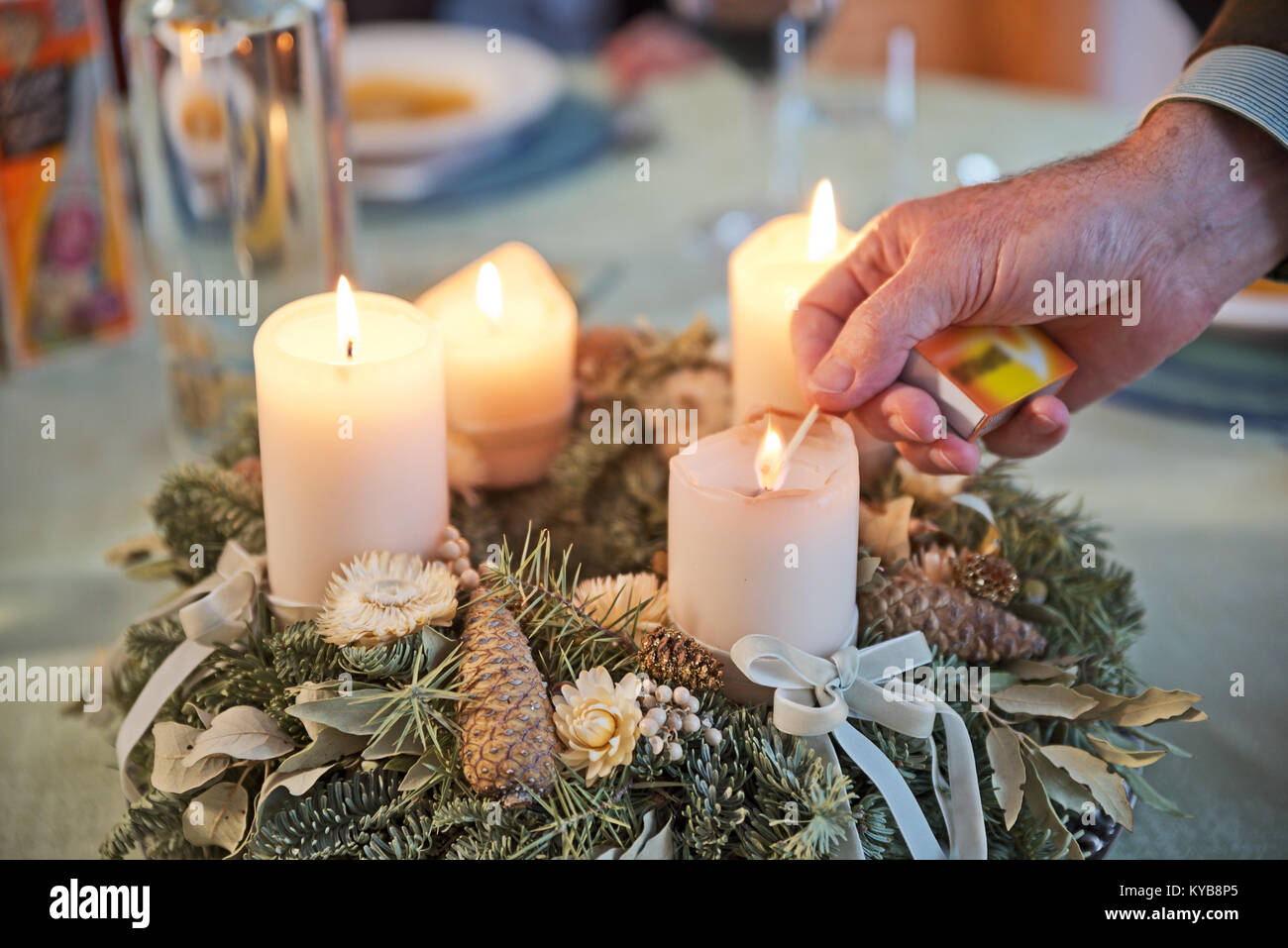 Person lighting the candles on a decorated Advent wreath with a match on a solemnly laid table, ready for a festive - Stock Image