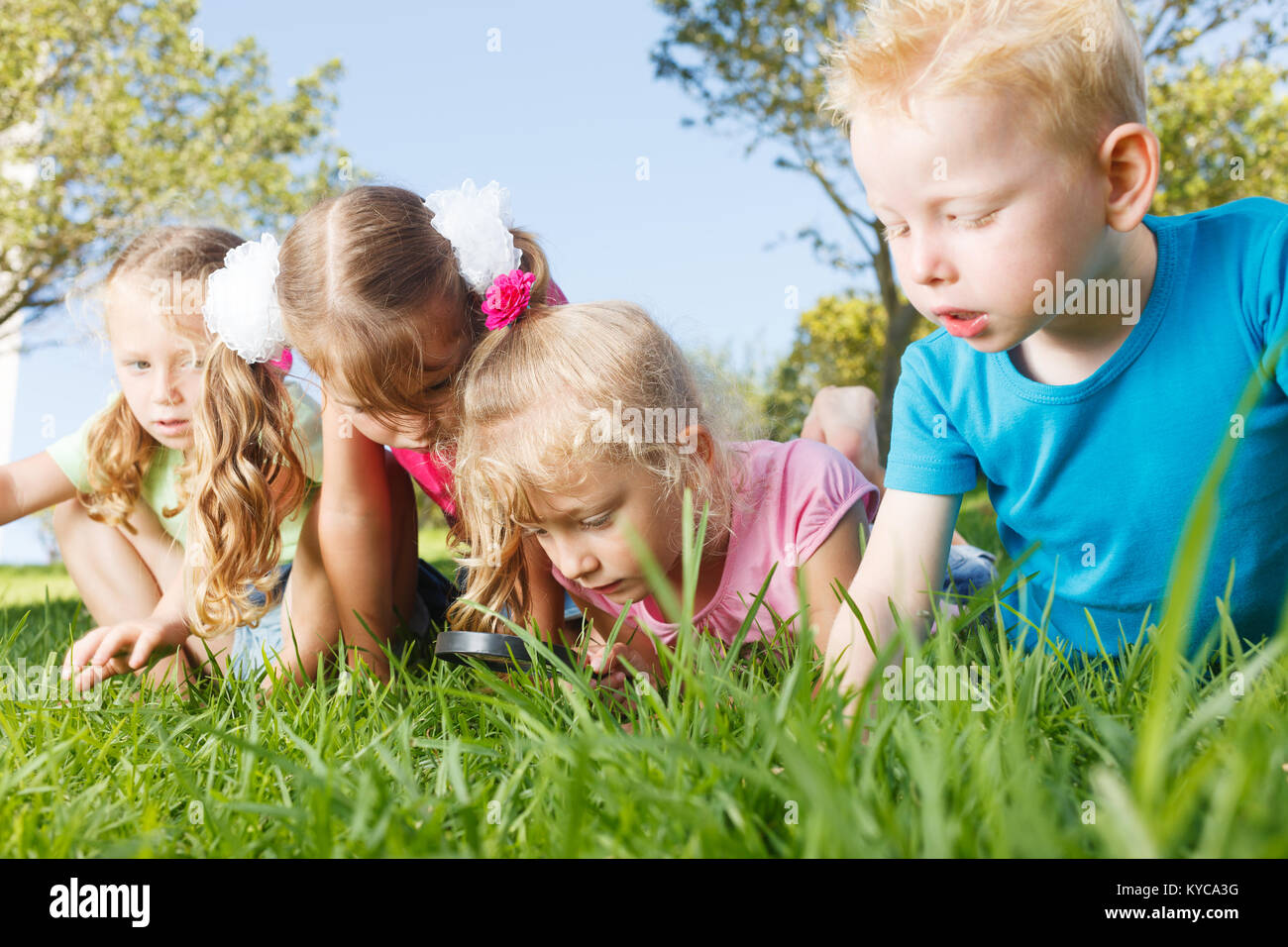 Preschoolers exploring the nature with magnifying glass - Stock Image
