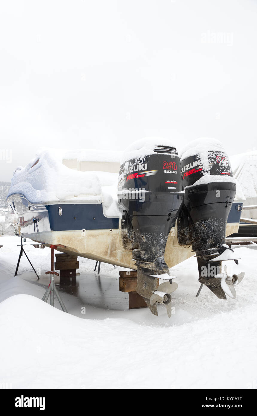Pleasure boat with two Suzuki outboard motors, stored on dry land at a marina during winter in Norway. - Stock Image