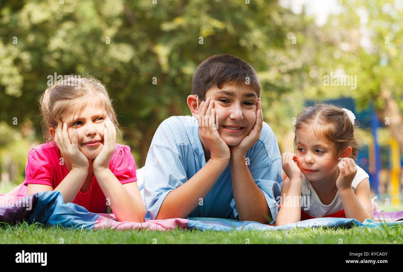 Group of three happy children lying on the grass - Stock Image