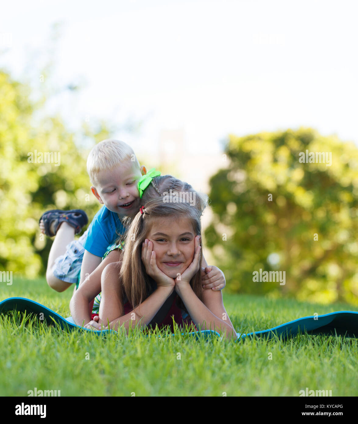 Happy children playing piggy back - Stock Image