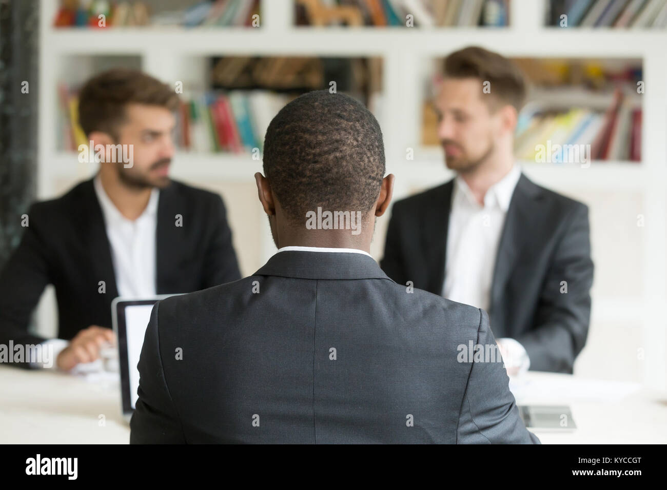 Rear view at african businessman against two caucasian men wearing suits, black vacancy candidate sitting his back - Stock Image