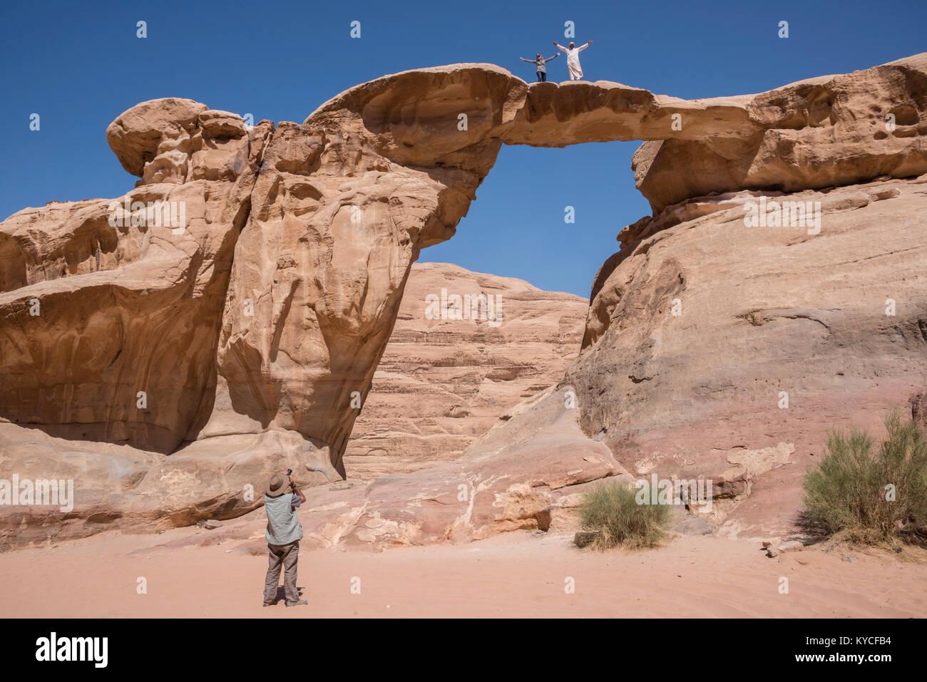 Tourists next to a Burdah bridge rock formation in the desert of Wadi Rum, Jordan - Stock Image