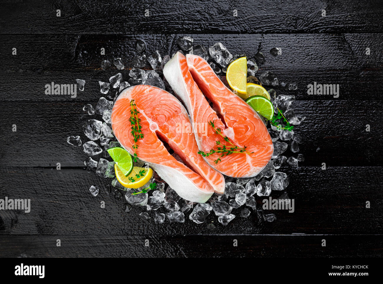 Salmon steaks on black wooden table background - Stock Image