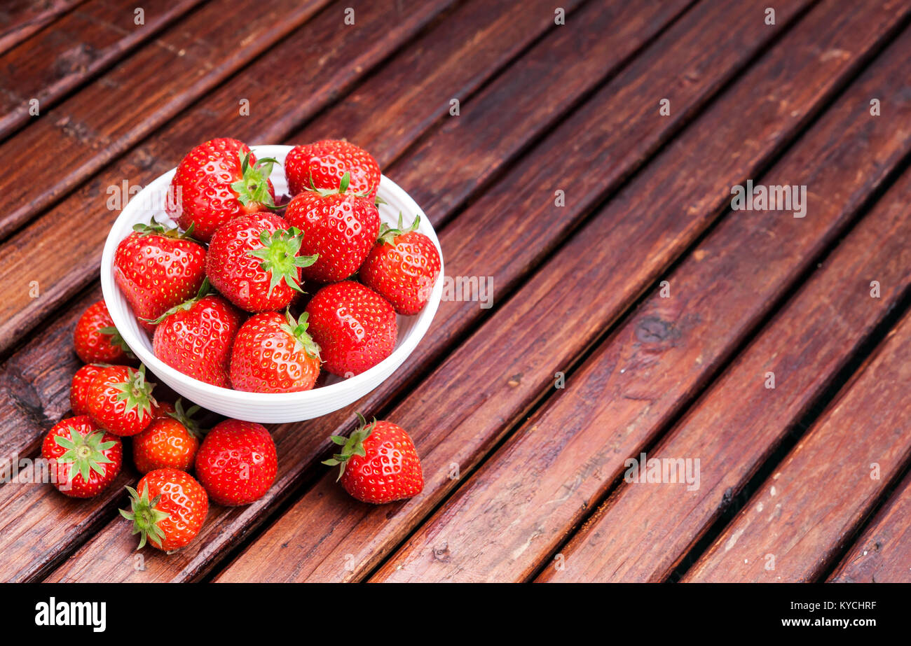 Strawberry in bowl on wooden table - Stock Image