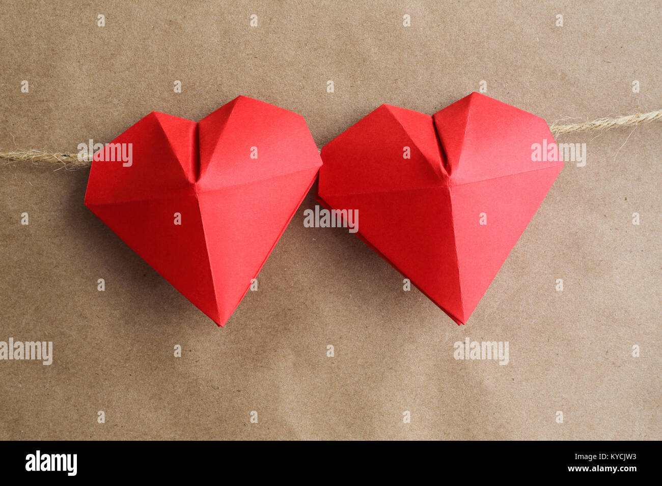 Red origami hearts on rope over paper background, Valentines
