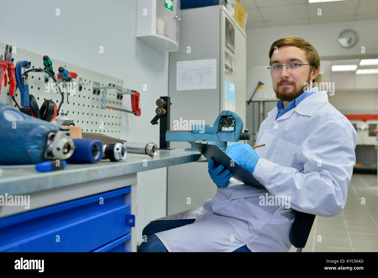 Portrait of young medical engineer posing in laboratory sitting by table with orthopedic equipment and looking at Stock Photo