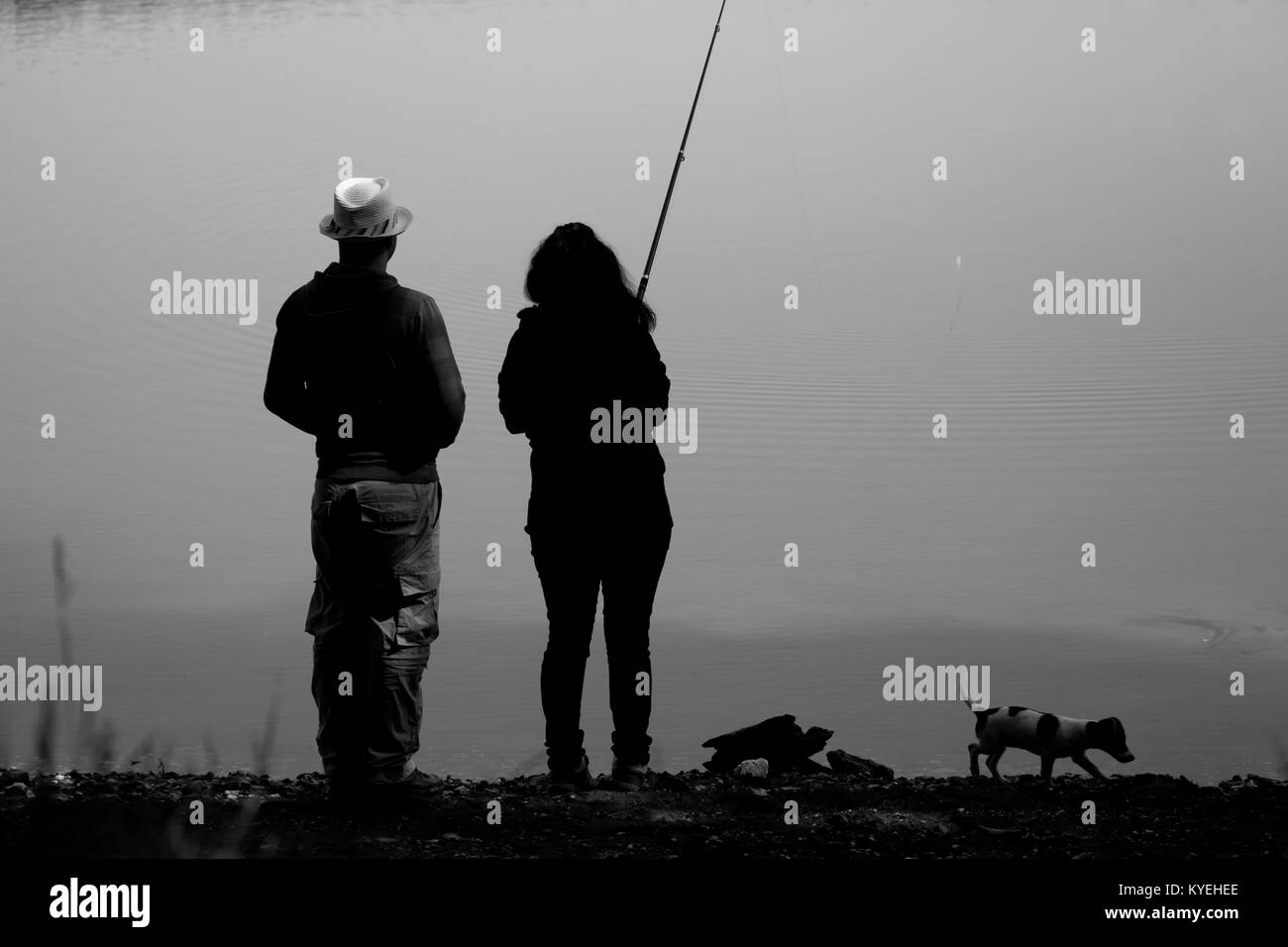 black and white landscape with couple and small dog fishing near small lake - Stock Image