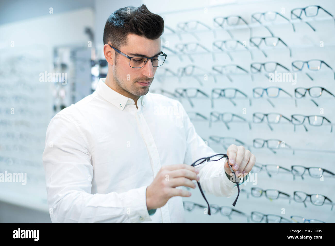 Serious man looking glasses frame in store - Stock Image