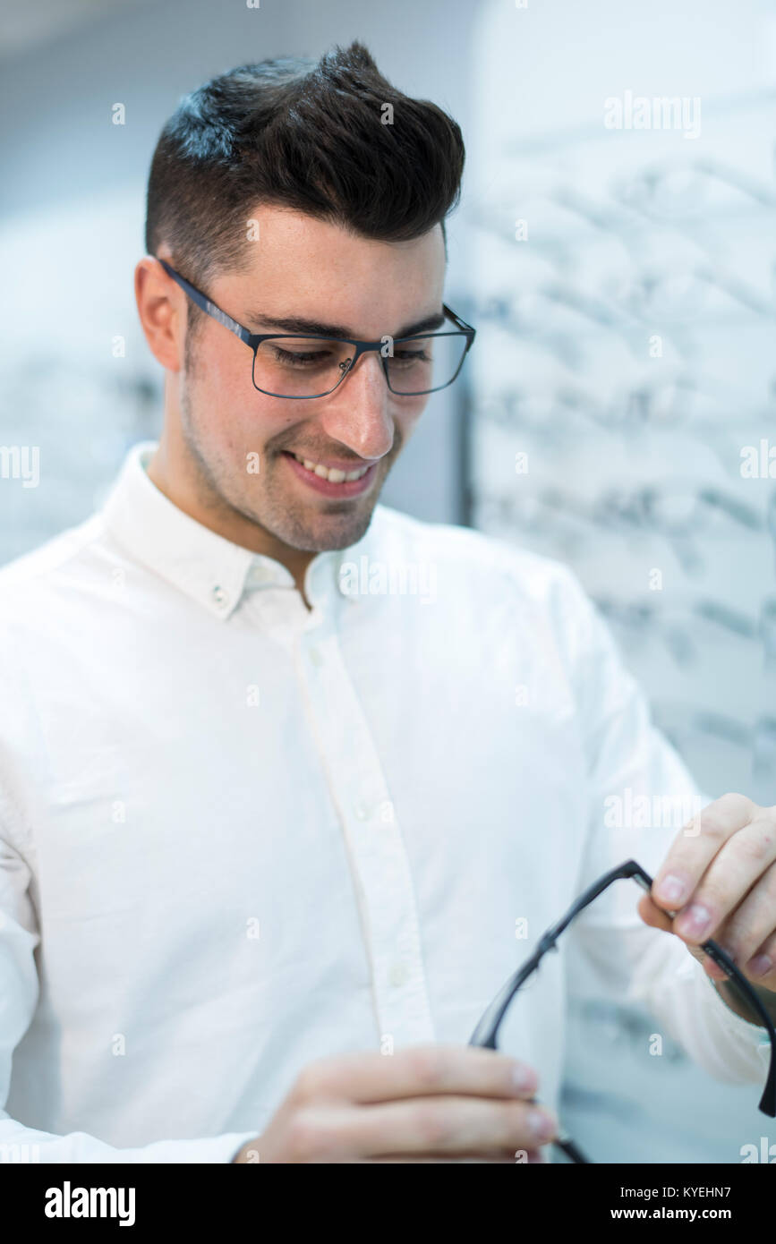 Smiling man looking glasses frame in store - Stock Image