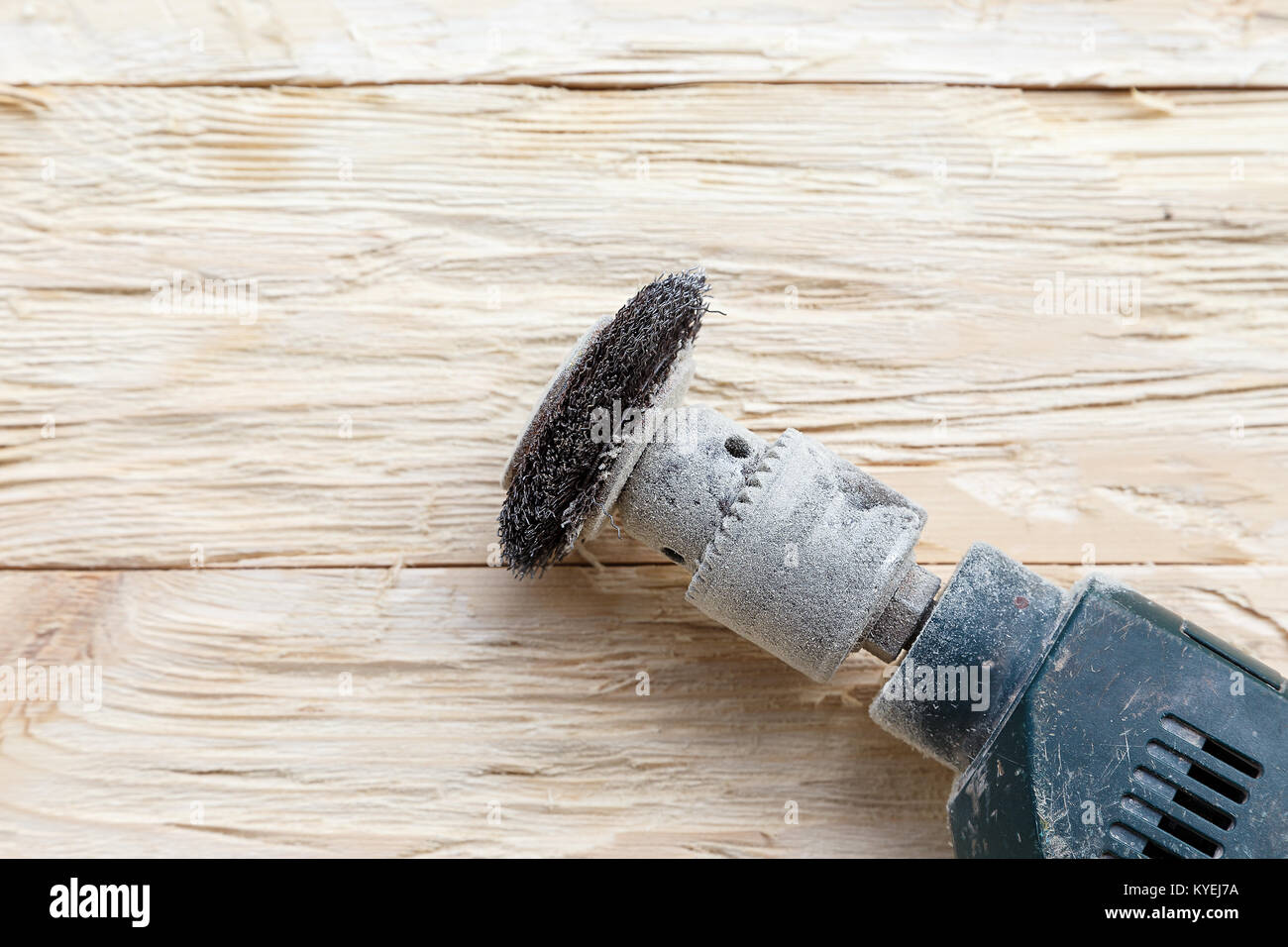 attachment on a drill, scrape, metal rotating brush. attachment is on a rough wooden surface - Stock Image