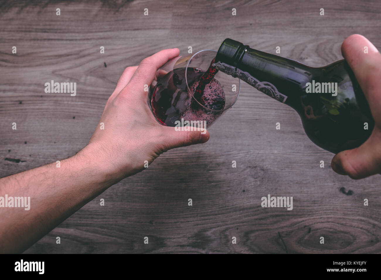 View from the top of one hand holding a red wine bottle and pouring it into a glass - Stock Image