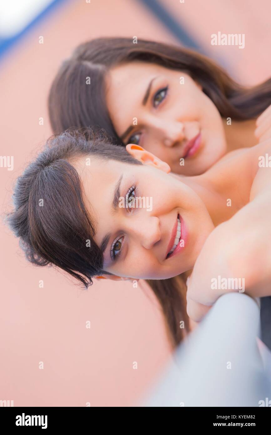 Girlfriends portraits eyes-contact looking at camera happy and smiling - Stock Image