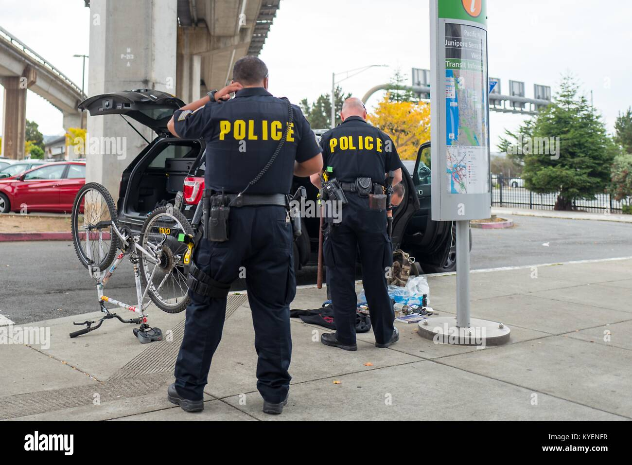 Two Bay Area Rapid Transit (BART) police officers are viewed from behind, with an overturned bicycle and bag with - Stock Image