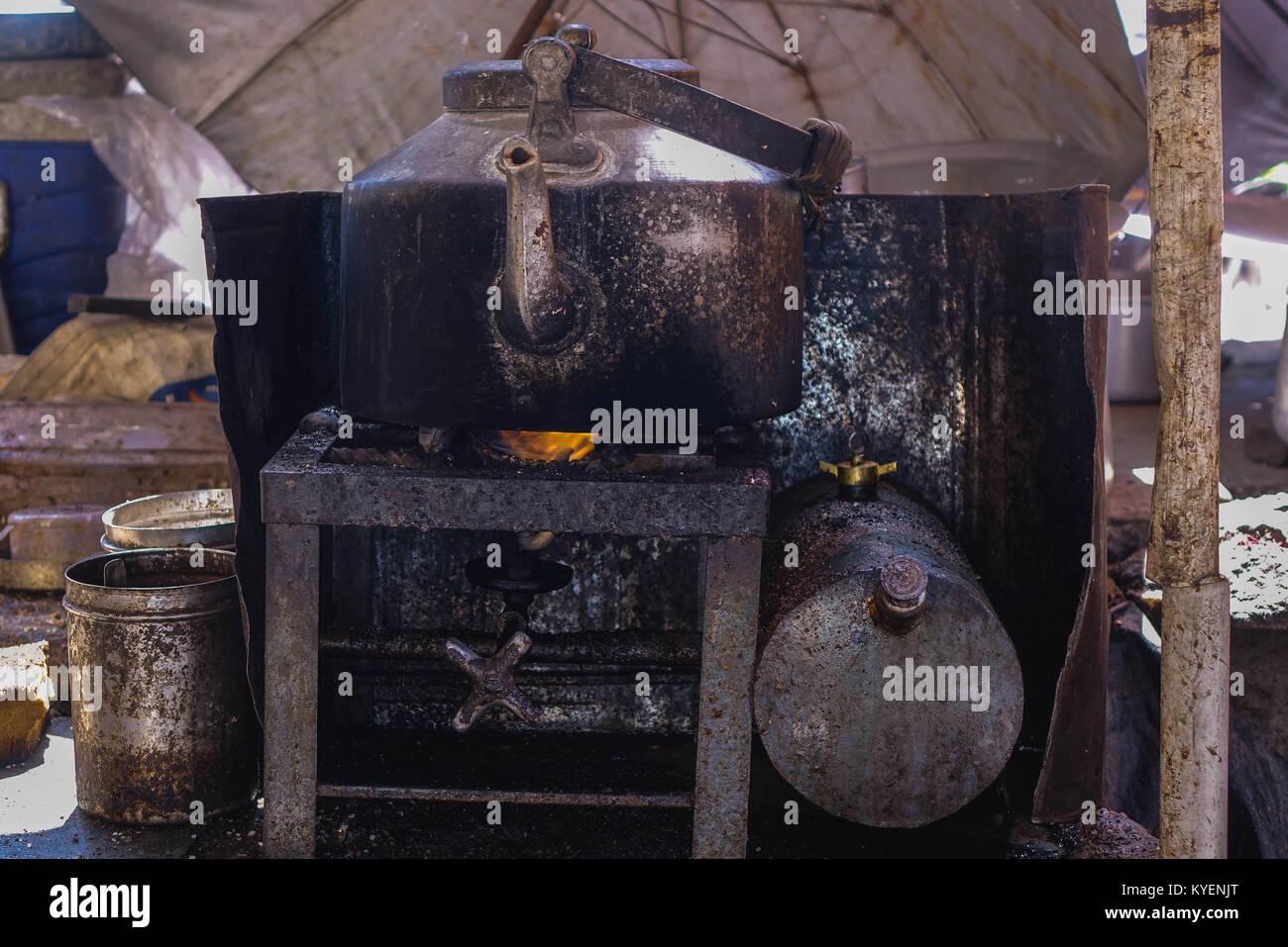 A darkened and old Aluminium tea kettle on kerosene stove - Stock Image