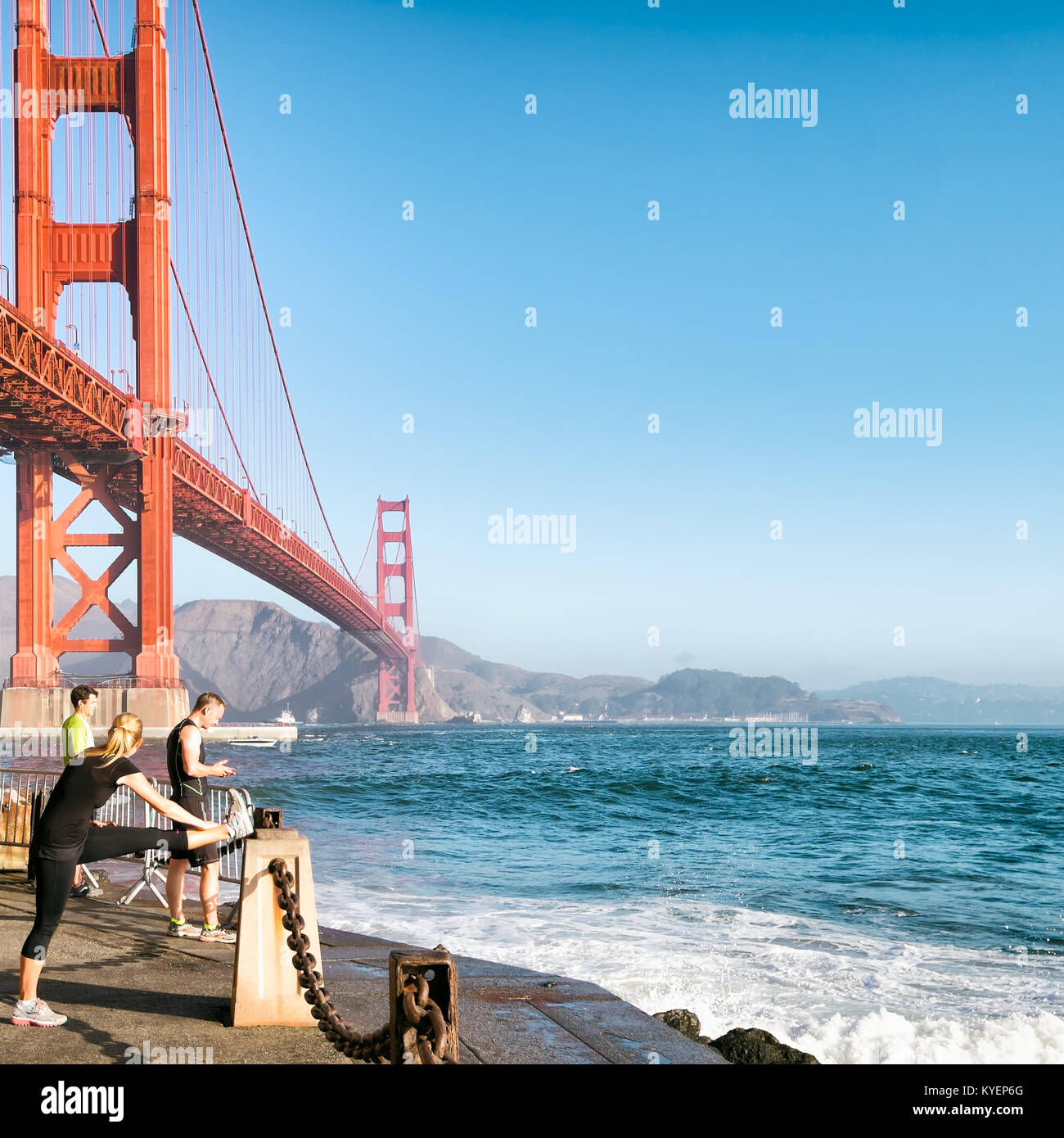 SAN FRANCISCO, CA- Oct. 11, 2015: Golden Gate Bridge. Runners below the bridge at Fort Point stop and stretch at - Stock Image