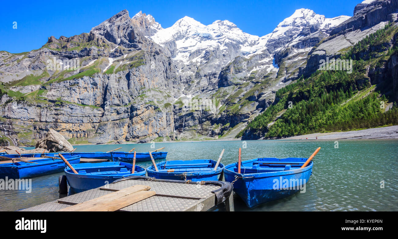 Sunny Summer Activities and recreation, rowing blue boats while enjoying beautiful Swiss alps view on Lake Oeschinen - Stock Image