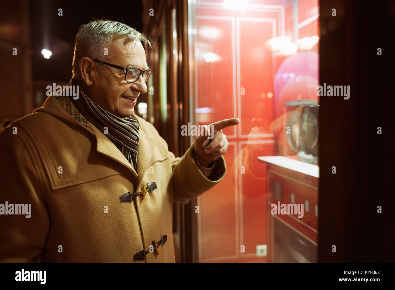 Senior man is shopping and looking at store front. - Stock Image