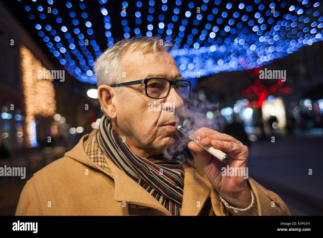 Senior man is smoking electronic cigarette in the city. - Stock Image