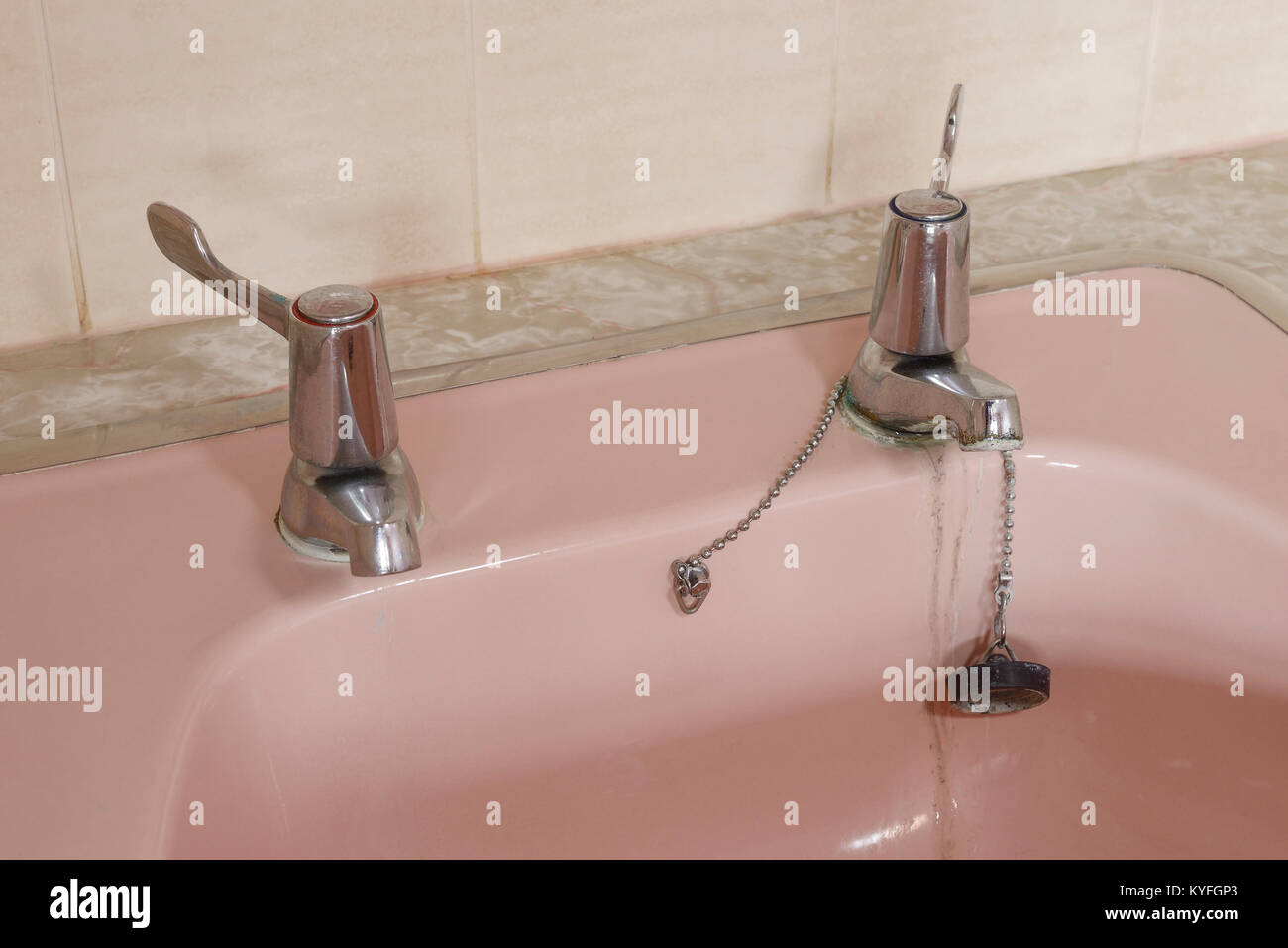 Close up detail of a domestic vanity unit hand basin in coral pink ceramic with silver taps with levers - Stock Image