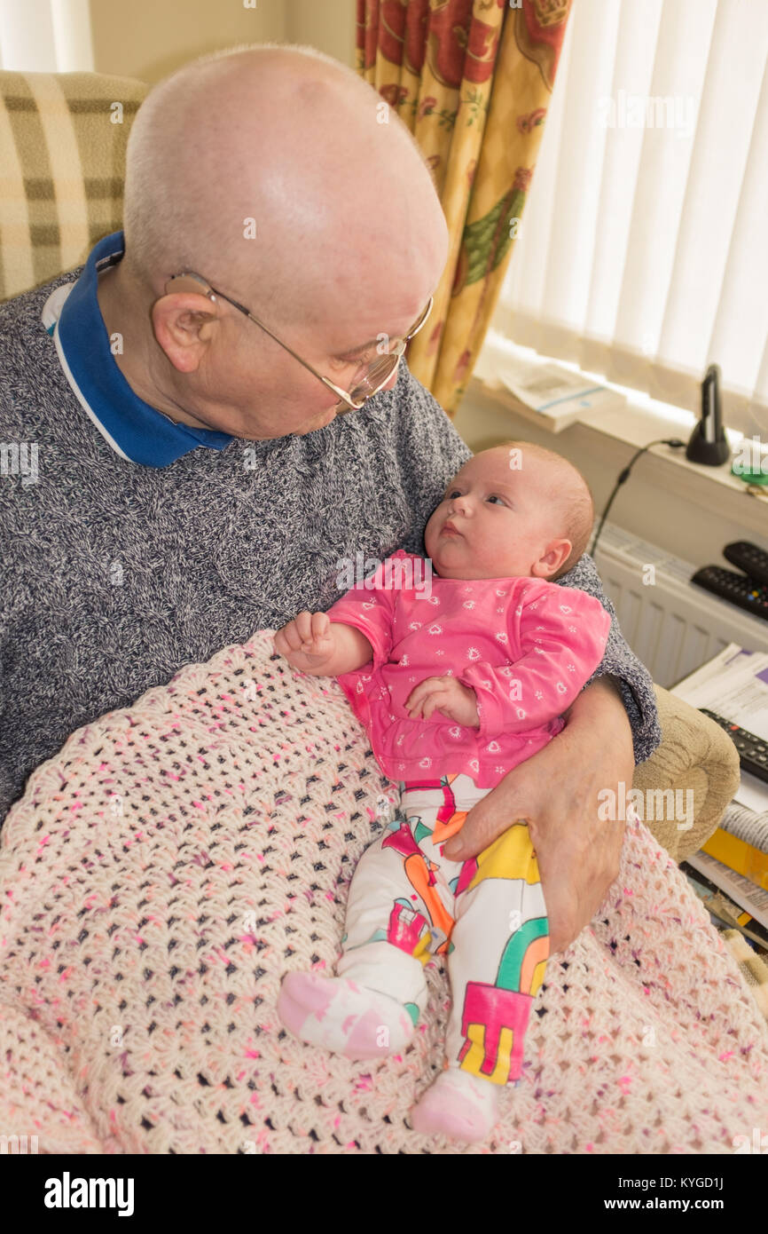 New born baby sitting on her great grandfather's lap, looking up at him - Stock Image