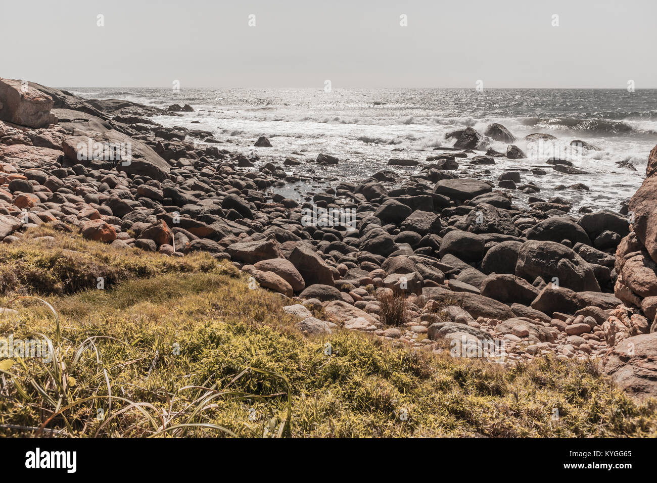 Rocky beach cove  ocean waves coastline summer  in vintage photo tones - Stock Image