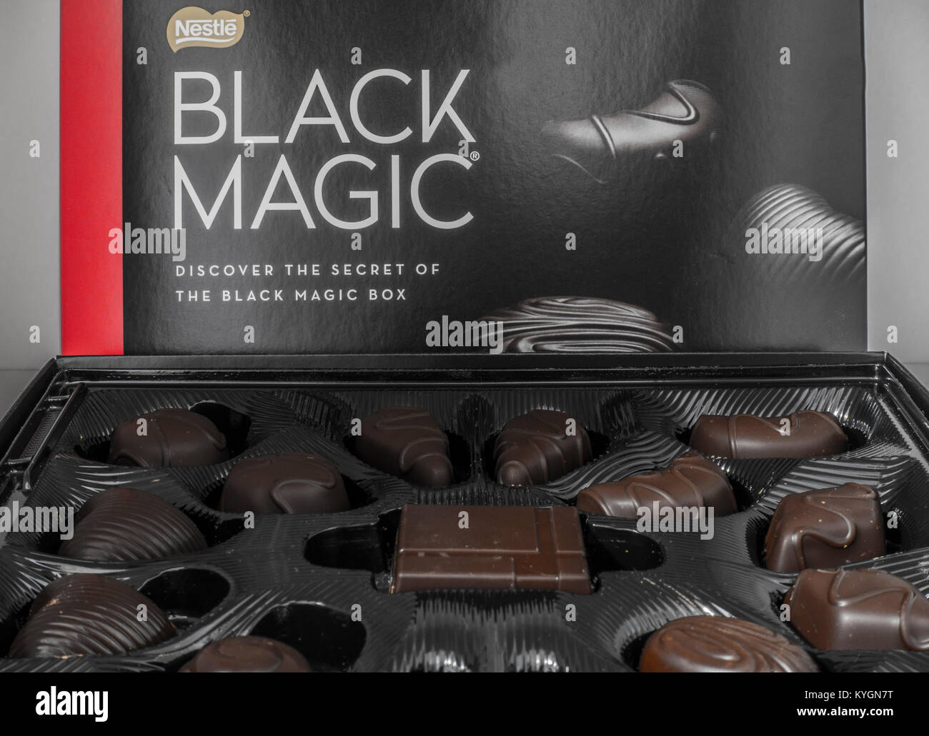 Nestlé Black Magic open box of dark chocolates. Closeup of the different shaped chocolate selection along with - Stock Image