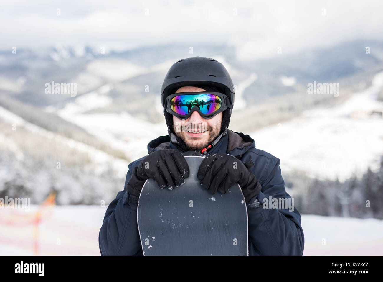 Snowboarder in ski suit and helmet with snowboard - Stock Image