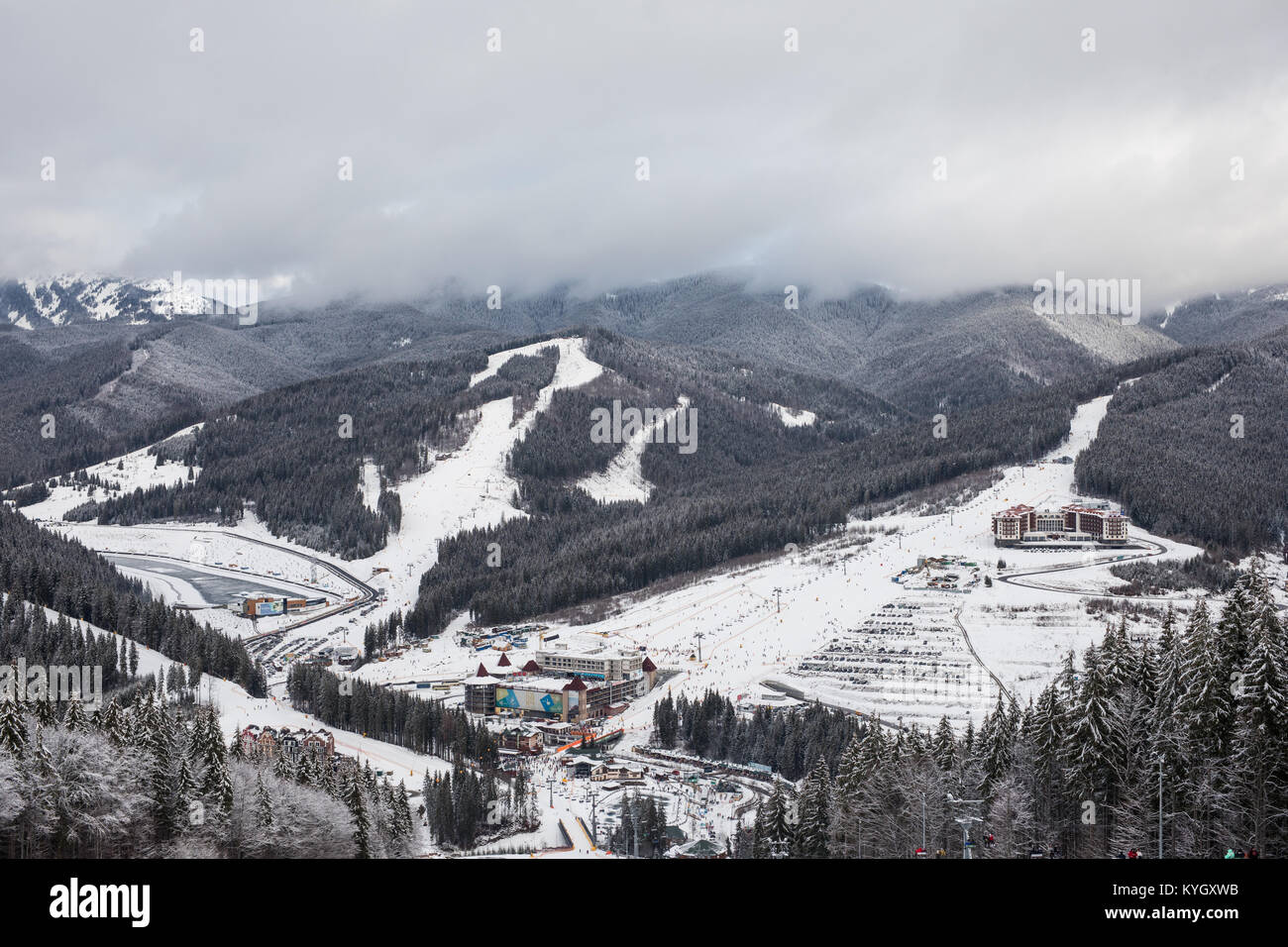 Panorama of the prepared ski slope among spruce forest on a background of mountain ranges and sky on ski resort Stock Photo