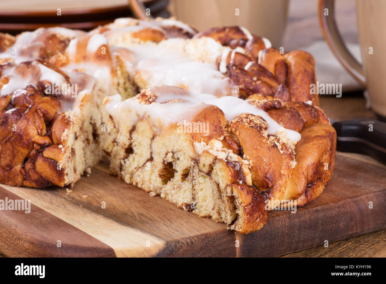 Slice of glazed struesel coffee cake on wooden platter with shallow depth of field - Stock Image