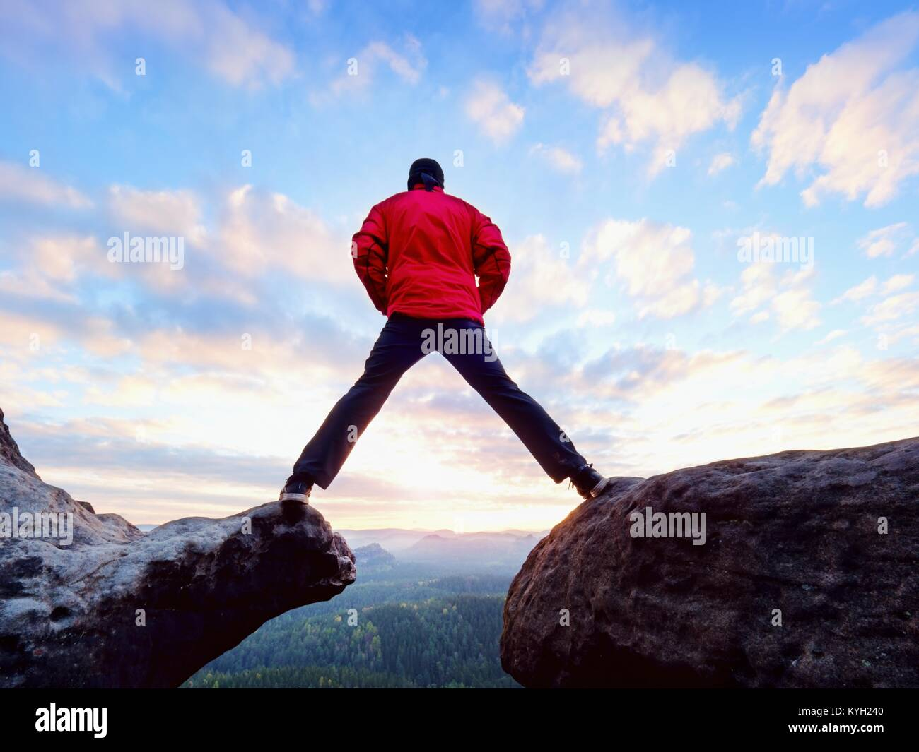 Man jumping from the mountain edge.  Man jumping off a cliff without rope. Risky moment. Rough rocky ground. - Stock Image