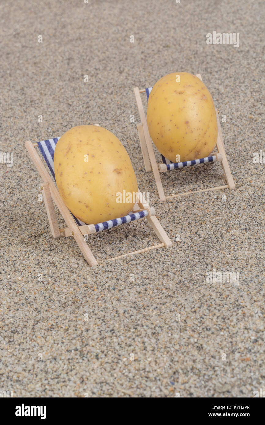 New potatoes on toy deckchair on sand - as visual metaphor for concept of 'couch potato', an inactive lifestyle, - Stock Image