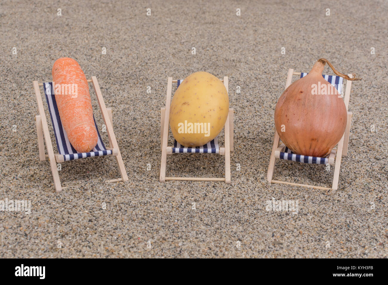 New potato, small carrot and onion on toy deckchairs on sand - as visual metaphor for concept of 'couch potato' - Stock Image