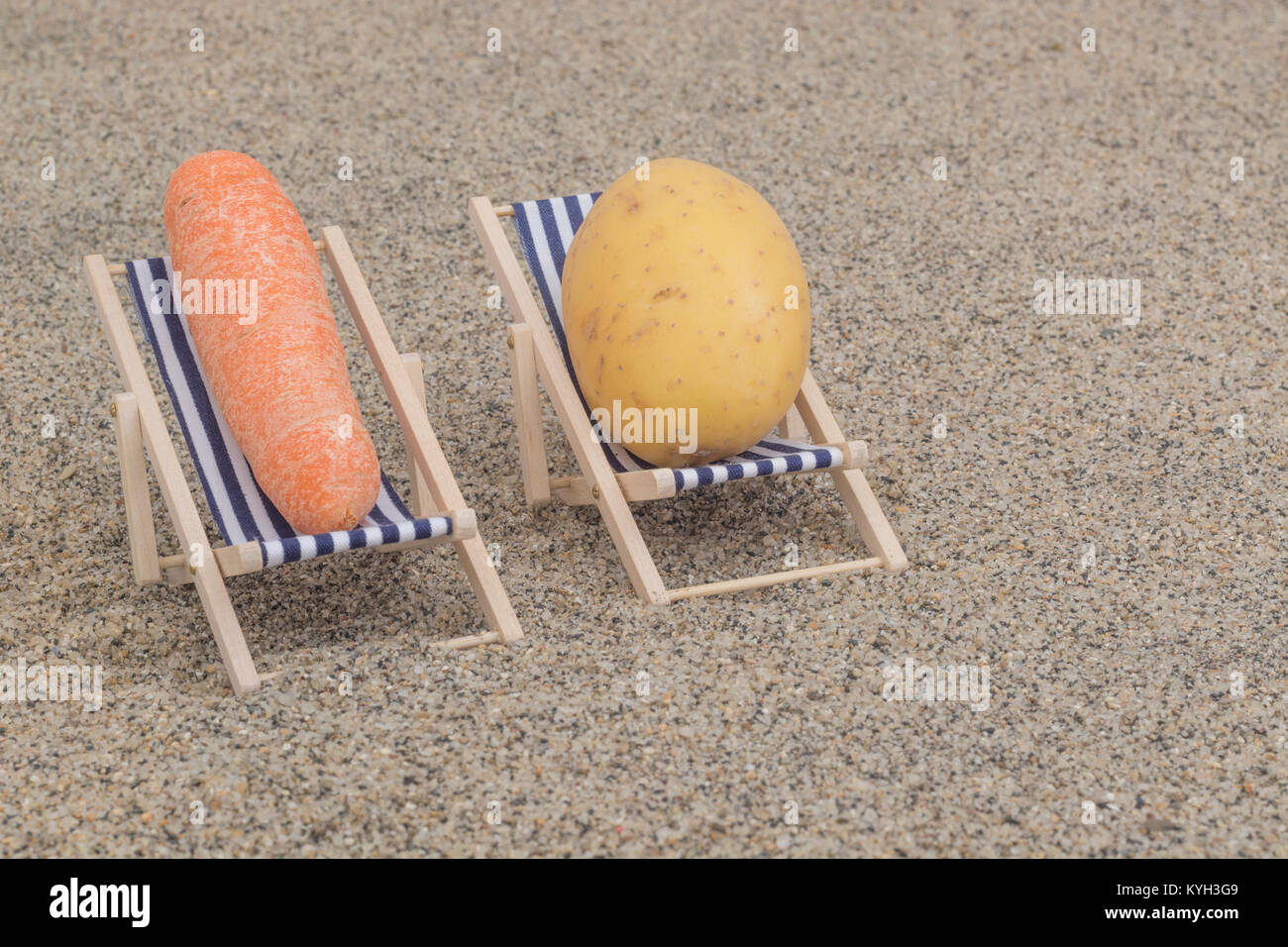 New potato and small carrot on toy deckchairs on sand - as visual metaphor for concept of 'couch potato' - Stock Image