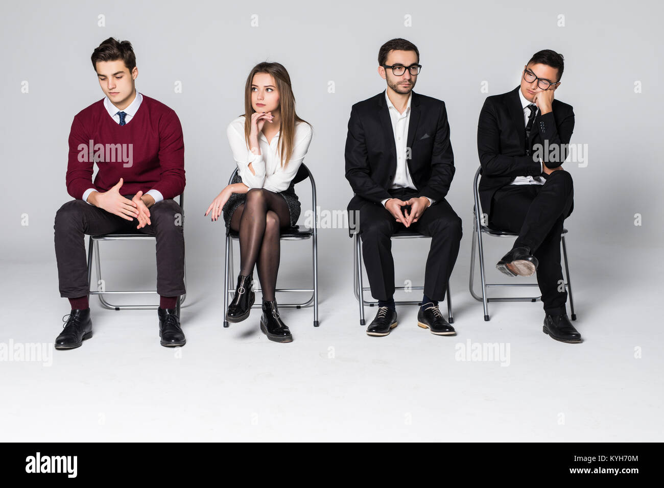 Group of people sitting on chairs waiting interviews - Stock Image
